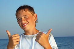 Smiling teenager boy against sea shows gesture ok Stock Photos