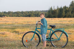 Smiling teenager boy holding bicycle in farm field. Smiling teenager boy holding a bicycle in farm field Royalty Free Stock Photography