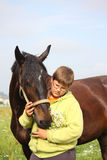 Smiling teenager boy with horses at the field Royalty Free Stock Photo