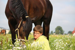 Smiling teenager boy with horses at the field Stock Photo