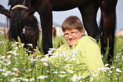 Smiling teenager boy with horses at the field Stock Image
