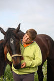 Smiling teenager boy with horses at the field Stock Images