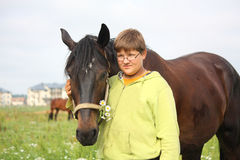 Smiling teenager boy with horses at the field royalty free stock photos