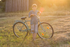 Smiling teenager boy standing with bicycle. Smiling teenager boy standing with a bicycle at sunset Royalty Free Stock Photos