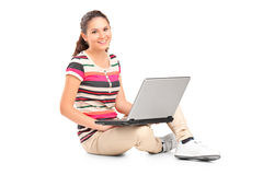 A smiling teenager doing her homework on a laptop Royalty Free Stock Photo
