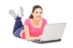 Smiling teenager doing her homework on a laptop Royalty Free Stock Images
