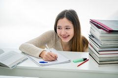 Smiling teenager doing her homework among stack of books stock photos