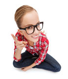 Smiling teenager in eyeglasses with finger up Stock Images