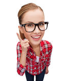 Smiling teenager in eyeglasses with finger up. Happiness and gesture concept - smiling teenager in eyeglasses with finger up, funny character with big head Royalty Free Stock Photo