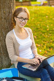 Smiling teenager in eyeglasses with laptop Stock Image