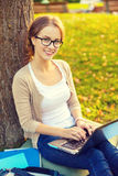 Smiling teenager in eyeglasses with laptop Stock Photos