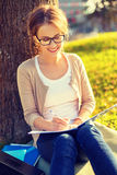 Smiling teenager in eyeglasses writing in notebook Royalty Free Stock Photo