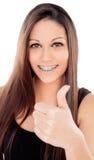 Smiling teenager girl with brackets saying Ok Stock Photography