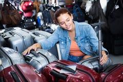 Smiling teenager girl choosing new large plastic luggage bag Stock Photography