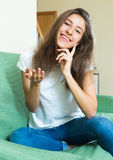 Smiling teenager girl on the couch. Portrait of cheerful young long-haired girl on the couch at home Royalty Free Stock Photos