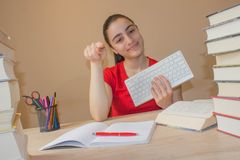 Girl doing homework at the table at home. Young Girl student with pile of books and notes studying indoors. Smiling teenager girl doing homework at the table at Royalty Free Stock Image