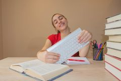 Girl doing homework at the table at home. Young Girl student with pile of books and notes studying indoors. Smiling teenager girl doing homework at the table at Royalty Free Stock Photography