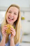 Smiling teenager girl eating sandwich in kitchen Royalty Free Stock Photography
