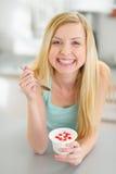 Smiling teenager girl eating yogurt in kitchen Stock Photo