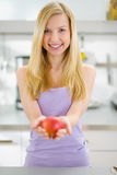 Smiling teenager girl giving apple in kitchen Royalty Free Stock Images