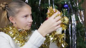 Teenage girl looking at Christmas garland. Smiling teenager girl looking at Christmas garland and brings it to the camera stock footage