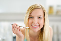 Smiling teenager girl with spoon of yogurt. Smiling teenager girl with blond hair with spoon of yogurt Royalty Free Stock Photography