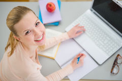 Smiling teenager girl studying in kitchen Royalty Free Stock Photography