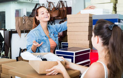 Smiling teenager girl taking box with pairs from seller in shoes Stock Images