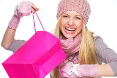 Smiling teenager girl in winter hat and scarf opening shopping bag Stock Photos