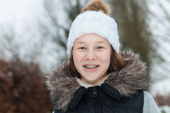 Smiling teenager girl in a winter park. Outdoor portrait of a smiling teenager girl in winter clothing Stock Image