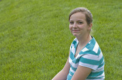 Smiling teenager on grass hillside Stock Images