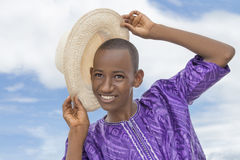Smiling teenager holding a boater straw hat Royalty Free Stock Photography