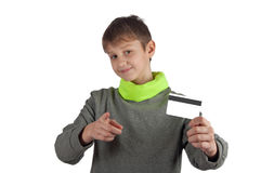 Smiling teenager holding white credit card and pointing towards you with finger. Isolated on white. Smiling teenager in grey, green sweater holding white credit Royalty Free Stock Images