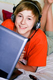 Smiling teenager with a laptop Stock Photography