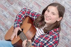Smiling teenager playing guitar. A smiling teenager playing an acoustic  guitar Stock Photo