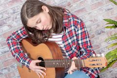 Smiling teenager playing guitar. A smiling teenager playing an acoustic  guitar Royalty Free Stock Photos