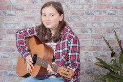 Smiling teenager playing guitar. A smiling teenager playing an acoustic  guitar Royalty Free Stock Photography