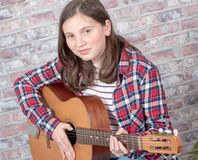 Smiling teenager playing guitar. A smiling teenager playing an acoustic  guitar Royalty Free Stock Photo