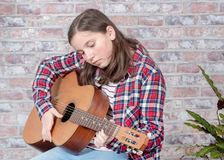 Smiling teenager playing guitar. A smiling teenager playing an acoustic  guitar Stock Image