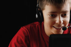 Smiling teenager playing on laptop Stock Photo