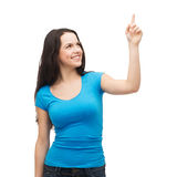 Smiling teenager pointing her finger up Stock Photo
