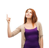 Smiling teenager pointing her finger up. Advertisement concept - attractive teenager in casual clothes pointing her finger up Royalty Free Stock Images