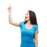 Smiling teenager pointing her finger up Royalty Free Stock Photography