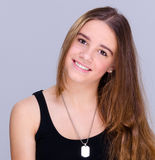 Smiling teenager portrait. Pretty teenager portrait isolated on grey background Stock Photography