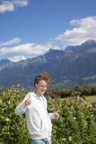 Smiling teenager posing thumbs up. A smiling 14 years old teenager posing with the thumbs up sign, photographed in the summer with the Alps of South Tirol in the Stock Photo