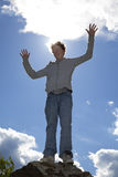Smiling teenager raising his arms Stock Images