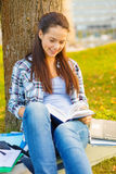 Smiling teenager reading book Stock Photos