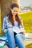 Smiling teenager reading book Stock Photos