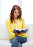 Smiling teenager reading book and sitting on couch Stock Photography