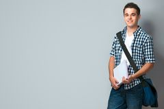 Smiling teenager with a schoolbag. Standing on wall background Stock Photography
